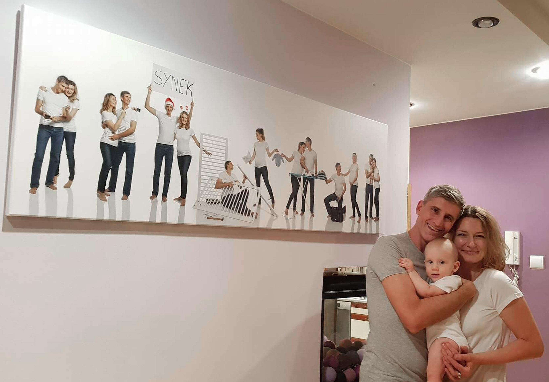 zdjęcie rodziców z synkiem w objęciach na ścianie wisi zdjęcie z sesji ciążowej